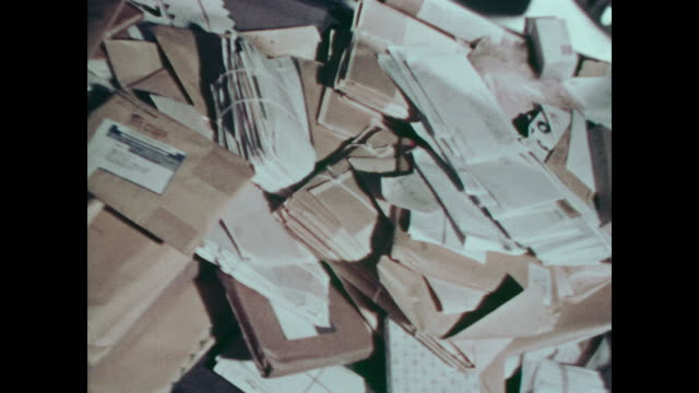 1967 mail falls from sacks onto sorting conveyer belt as female workers check individual letters - postamt stock-videos und b-roll-filmmaterial