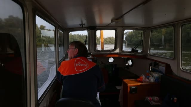 vidéos et rushes de a mail man for postnl nv steers a mail delivery barge on a river in de biesbosch netherlands on wednesday oct 2 view from a mail delivery barge as it... - post it