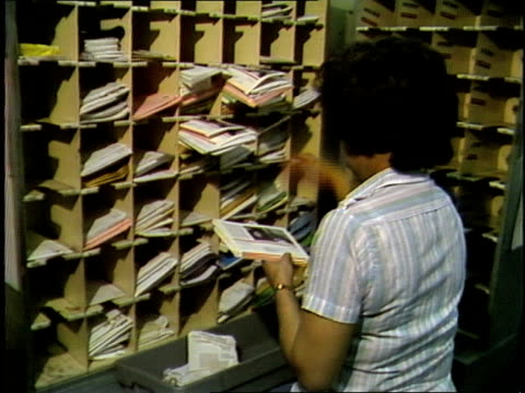 africanamerican adult female postal service employees sorting mail by hand into cubby holes pull back to several africanamerican male and female... - post structure stock videos & royalty-free footage