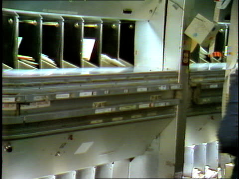 mail processing center: mail from sorting machines inside metal cubby holes; african-american adult female postal service employee grabbing stacks of... - united states postal service stock videos & royalty-free footage