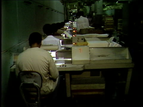 vídeos de stock e filmes b-roll de mail processing center: mail processing machines; mechanical arms grabbing envelopes; african-american adult male and female postal service employees... - afro americano