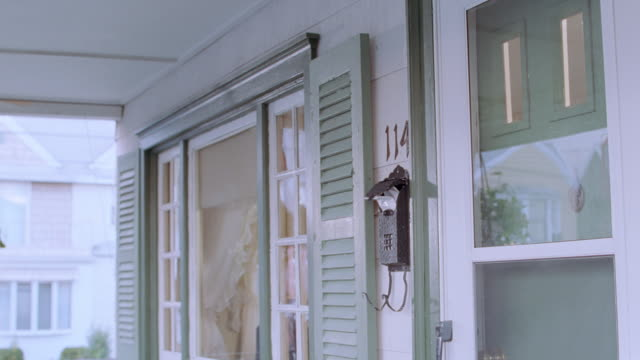 a mailbox hangs next to the front door of a home. - mailbox stock videos and b-roll footage