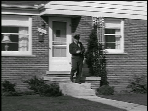 vidéos et rushes de b/w 1950 pan mailman delivering letter to suburban house + waving to dog + man in delivery van - facteur