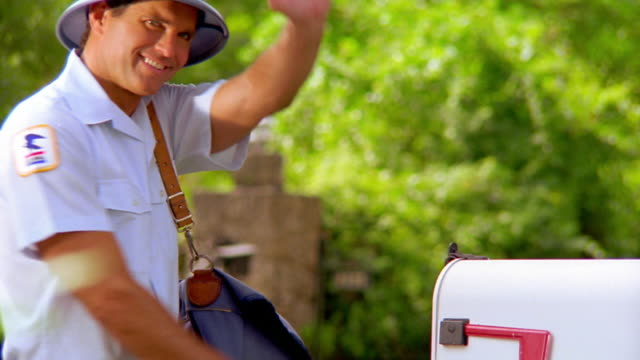 vidéos et rushes de ms mailman putting mail in mail box + waving - facteur