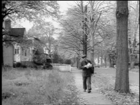 vidéos et rushes de b/w 1943/44 mailman walking on suburban sidewalk looking at mail / springfield, nj / newsreel - facteur