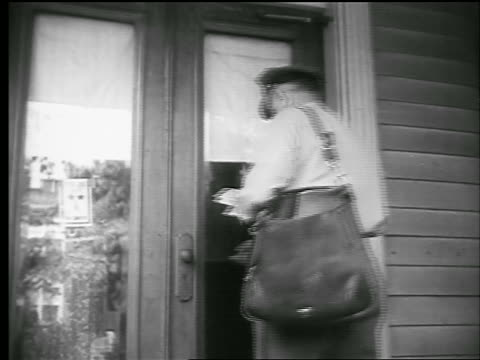 vidéos et rushes de b/w 1944 rear view mailman walking up to door of house / woman answers + takes mail / newsreel - facteur