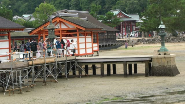 main buildings of the  itsukushima shrine connected by boardwalks and supported by pillars above the sea, japan - bassa marea video stock e b–roll