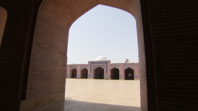 Main entrance to Shah Jahan mosque as seen through arch in opposing courtyard Available in HD.