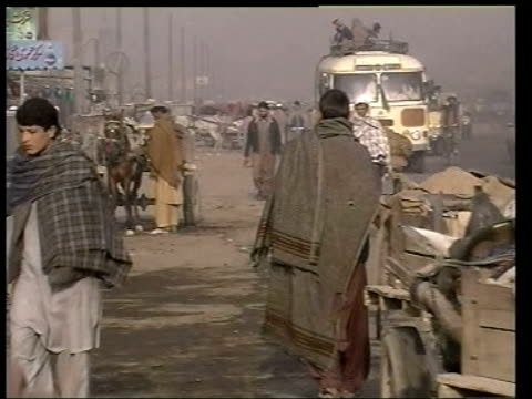 vidéos et rushes de main events/uk troops speculation; itn afghanistan: kabul: ext gv people about at open-air street market tlms vegetable traders sitting on ground... - kaboul
