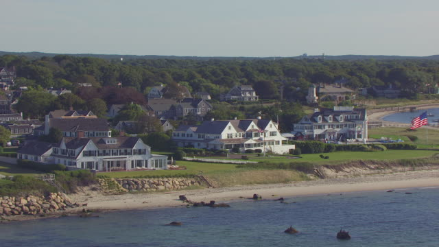 WS AERIAL POV Main house and taylor swift house with American flag near coastline / Hyannis, Massachusetts, United States