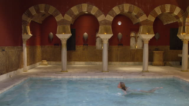 WS main pool hall of traditional Arab baths, young woman in bikini enters pool frame right, swims one length; turns around and stops halfway; stands up and smiles to camera