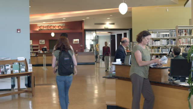 ws ts main public area in modern public library looking towards check out counter / rancho mirage, california, usa - 吊り照明点の映像素材/bロール
