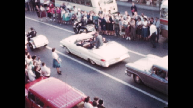 of main street in springfield, ohio lined with cars and people who watch as john. f. kennedy as he waves to the crowd from an open air motorcade.... - john f kennedy video stock e b–roll