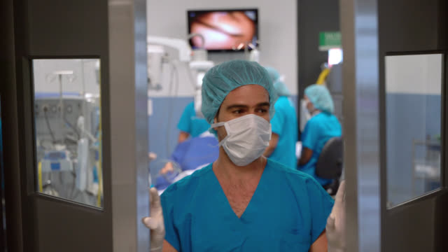 main surgeon leaving the operating room and opening the door after a successful surgery - leaving hospital stock videos & royalty-free footage
