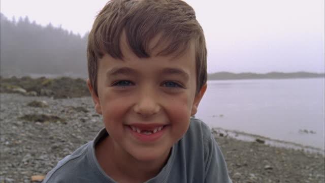 cu, ms, usa, maine, north haven, boy (6-7) running on beach - sorriso aperto video stock e b–roll