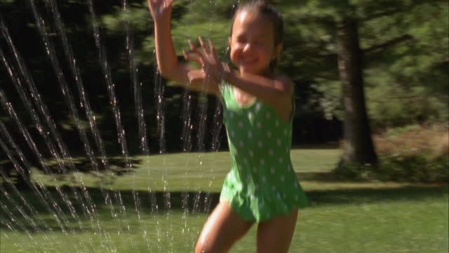 cu, pan, usa, maine, yarmouth, brother (6-7) and sister (4-5) jumping over backyard sprinkler - swimming costume stock videos and b-roll footage