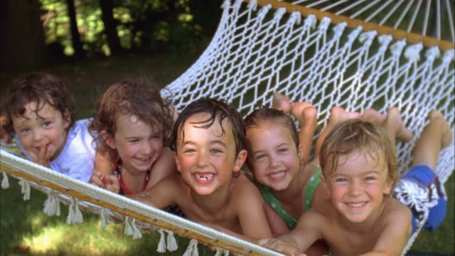 vídeos de stock, filmes e b-roll de cu, zi, focusing, usa, maine, yarmouth, five smiling children (2-3, 4-5, 6-7) with wet hair lying in hammock - barefoot