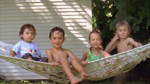 MS, USA, Maine, Yarmouth, Four smiling children (2-3, 4-5, 6-7) with wet hair sitting in hammock