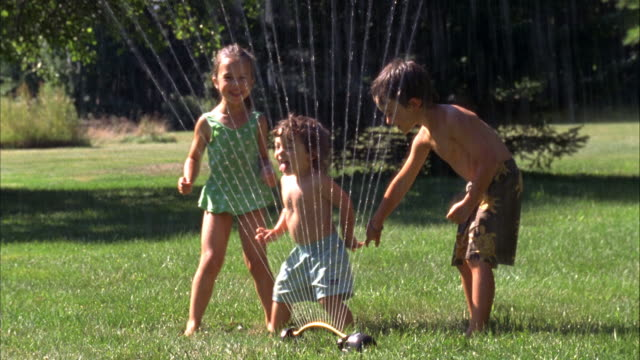 ms, usa, maine, yarmouth, three children (2-3, 4-5, 6-7) playing in backyard sprinkler - lawn stock videos & royalty-free footage
