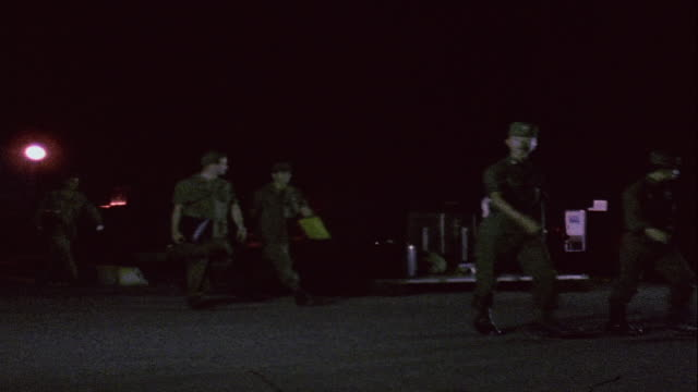 ws maintenance mechanics and crew walking to stations at nighttime airfield / da nang vietnam - ダナン点の映像素材/bロール