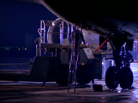 vídeos de stock e filmes b-roll de maintenance vehicle parked alongside stationary aircraft on runway as technician makes checks with torch - chassi