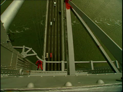 a maintenance worker rappels down the face of the san francisco oakland bay bridge as traffic passes below. - abseiling stock videos & royalty-free footage