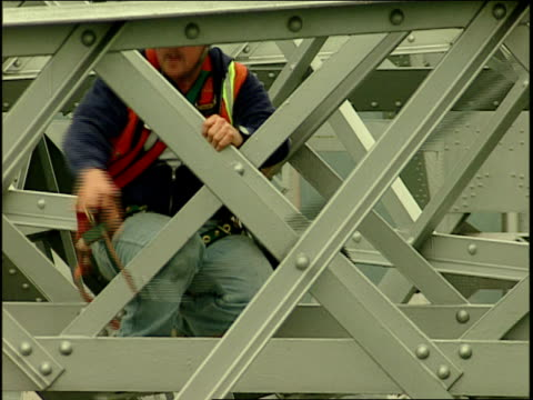 a maintenance worker secures his safety harness to a rope while working on the bay bridge. - safety harness stock videos & royalty-free footage