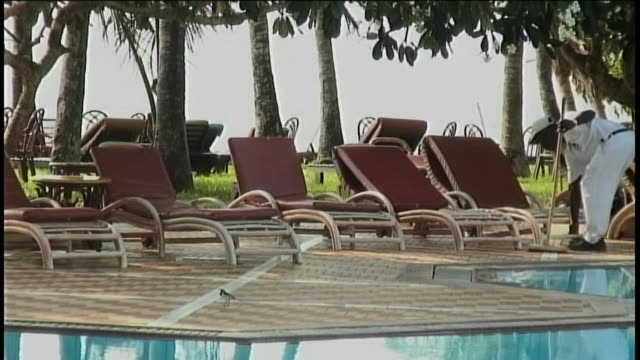 stockvideo's en b-roll-footage met a maintenance worker sweeps around lounge chairs next to a pool. - alleen één mid volwassen man
