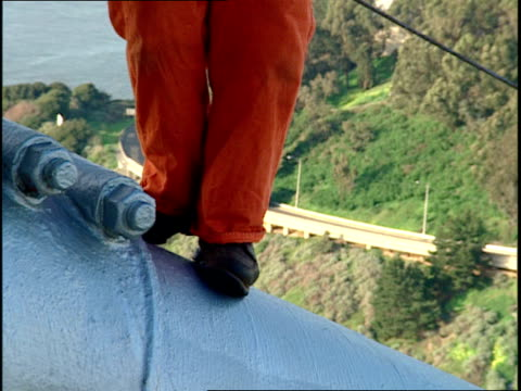 a maintenance worker wearing a safety harness walks along a cable on the san francisco bay bridge. - safety harness stock videos & royalty-free footage