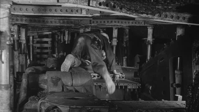 1964 B/W Maintenance workers overhaul power loader in coal mine / United Kingdom