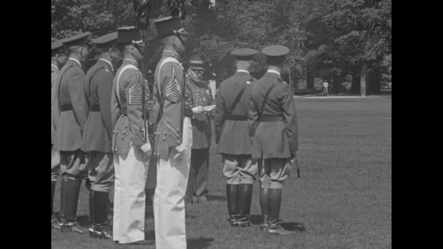 Maj Gen William Ruthven Smith reads from document at outdoor ceremony with cadets and officers standing at attention at left / Note exact month/day...