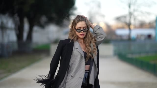 maja malnar wears mirrored sunglasses rings necklaces a black coat a black quilted clutch shiny black leather pants a black and white gingham jacket... - gingham stock videos & royalty-free footage