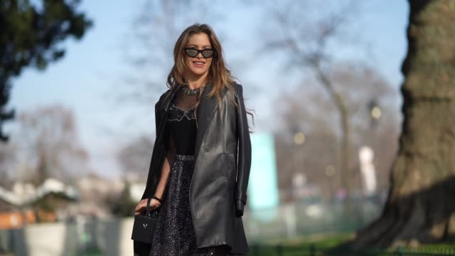 maja malnar wears sunglasses, a black cube bag, a black leather jacket, a black lace mesh glitter dress with a pleated part, outside elie saab,... - paris fashion week - haute couture spring/summer 2020点の映像素材/bロール