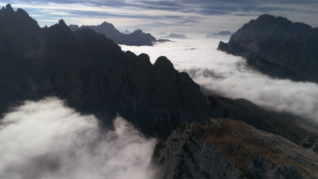 majestic aerial perspective showing mountainous terrain surrounded by clouds, dolomites, italy - tre cimo di lavaredo stock videos & royalty-free footage