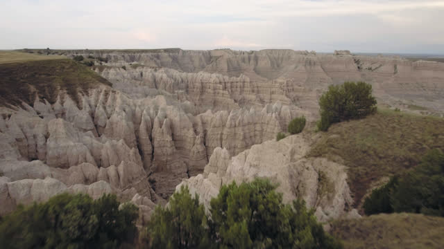 drone. majestic aerial view of trees and grass in badlands national park flying towards steep rock formation canyons - national landmark stock videos & royalty-free footage