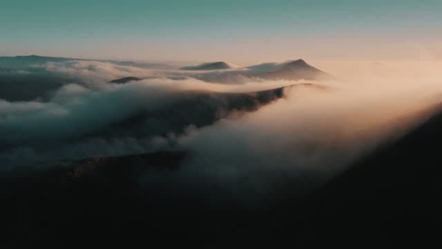 vídeos de stock e filmes b-roll de majestic aerial view showing a volcanic landscape surrounded by clouds at dawn, lanzarote, spain - beauty in nature
