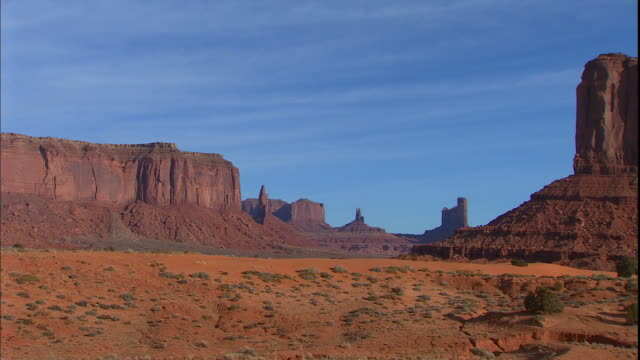 majestic buttes rise up from the desert floor in monument valley. - southwest usa stock videos and b-roll footage