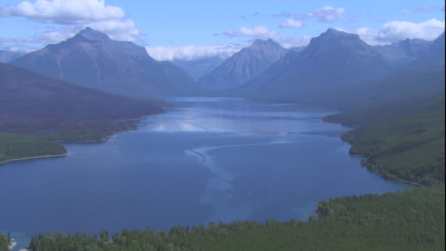 majestic mountains surround a lake in glacier national park, montana. available in hd. - glacier national park us stock videos and b-roll footage
