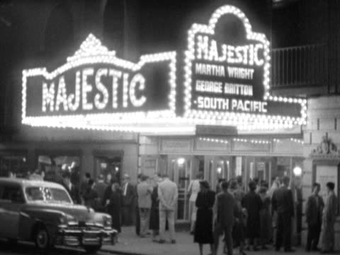 majestic theatre w/ lit marquee lights for 'south pacific' w/ various people standing by entrance taxicab pulling up to front cars passing on west... - ブロードウェイ点の映像素材/bロール