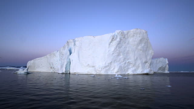 majestic view of iceberg at disko bay against blue sky - 氷山点の映像素材/bロール