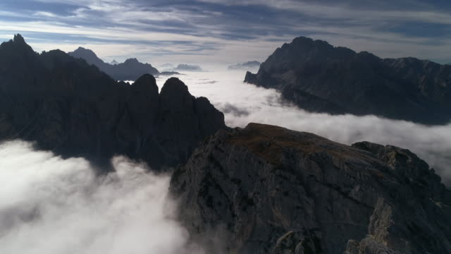 majestic views of mountain terrain surrounded by clouds, dolomites, italy - tre cimo di lavaredo stock videos & royalty-free footage