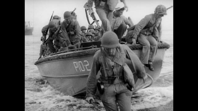 vídeos de stock e filmes b-roll de / major general alexander vandegrift narrates as marines climb from ship down to dingy weighed down by packs and rifles / ocean full of battle ships... - fuzileiro naval