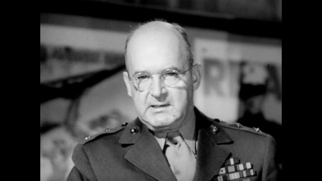 vídeos de stock, filmes e b-roll de / major general alexander vandegrift standing behind a metal desk with military recruitment posters in the background / discusses his time in command... - 1943