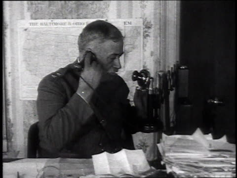stockvideo's en b-roll-footage met major general glenn sitting at desk speaking into oldfashioned vertical telephone / glenn and another man sitting at desk working - chillicothe