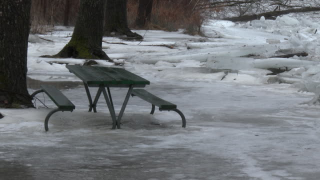 a major ice jam along the housatonic river in new milford connecticut causes river water to be pushed on shore and into a local park where it freezes... - picnic table stock videos & royalty-free footage