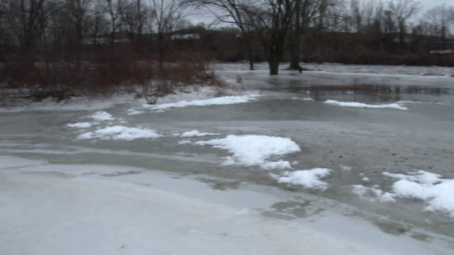 A major ice jam along the Housatonic River in New Milford Connecticut causes water to inundate a local park bordering the river where it freezes in...