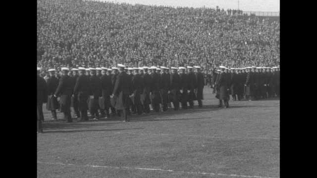 """majorette with sash, """"notre dame"""" stands in front of a marching band on the field at municipal stadium, with tens of thousands of people in the... - 士官候補生点の映像素材/bロール"""