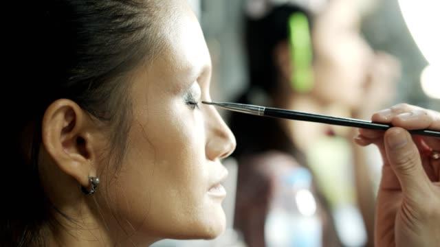 メイクアップアーティストは、美しい女性の顔にアイアイシャドウパウダーを適用します - メイクアップアーティスト点の映像素材/bロール