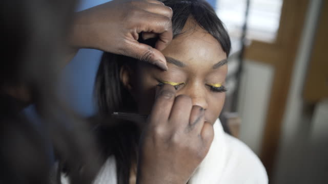 A make -up artist applying eyelashes to a young woman.