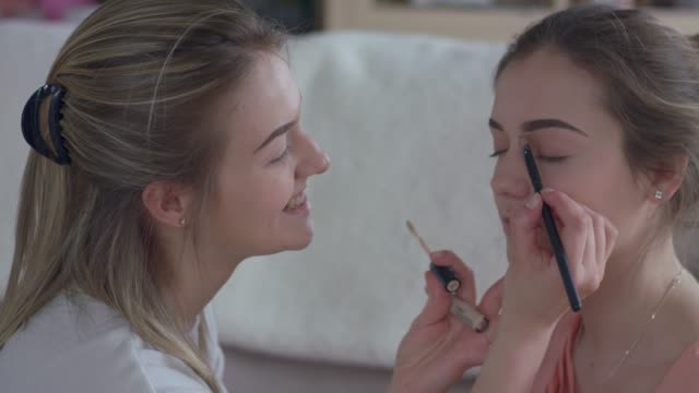 make up artist applying eyeshadow on a model while filming a video tutorial - tutorial stock videos & royalty-free footage